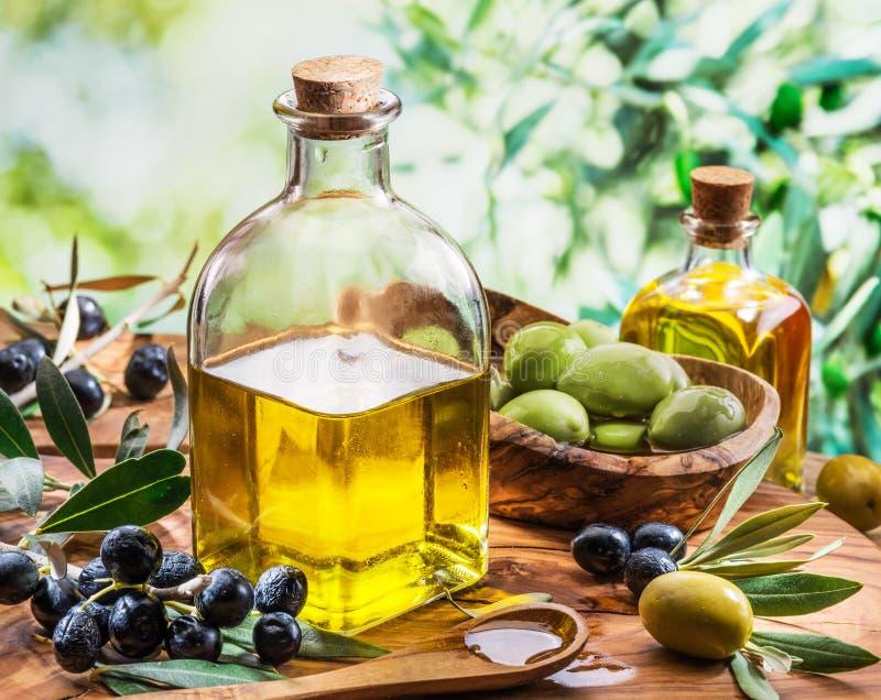 L'olio d'oliva e le bacche sono sulla tavola di legno nell'ambito dell'oliva TR fotografia stock