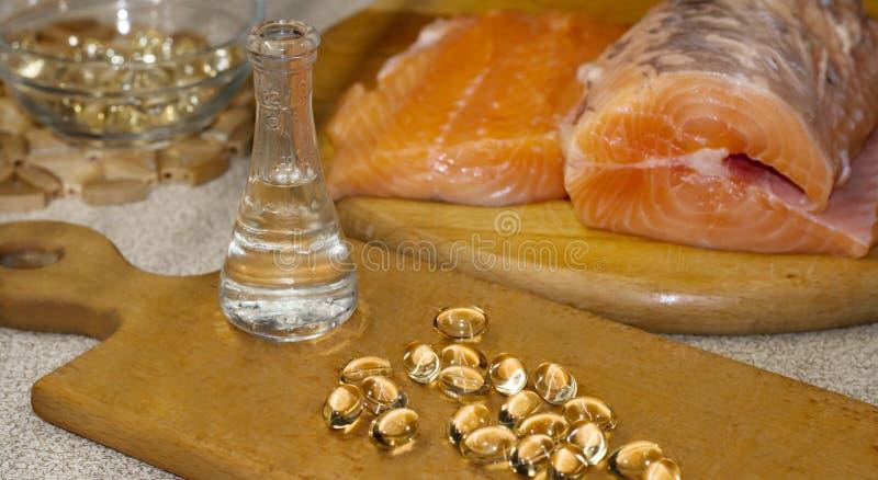 L'olio di pesce è liquido ed in capsule dal salmone Pesce del salmone rosso fresco su un tagliere di legno Olio di Omega 3 e di O fotografia stock libera da diritti
