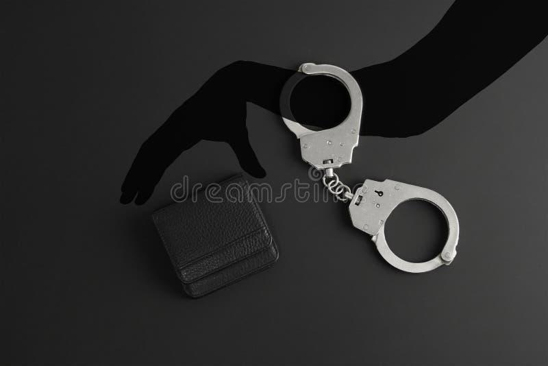L'ombra della mano umana in manette cerca di rubare il portafoglio in pelle nera, concetto di sicurezza finanziaria o commerciale immagini stock
