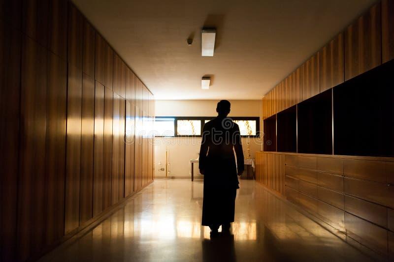 L'ombra di giovane sacerdote si è vestita nel nero che cammina da solo nella chiesa lunatica scura immagini stock