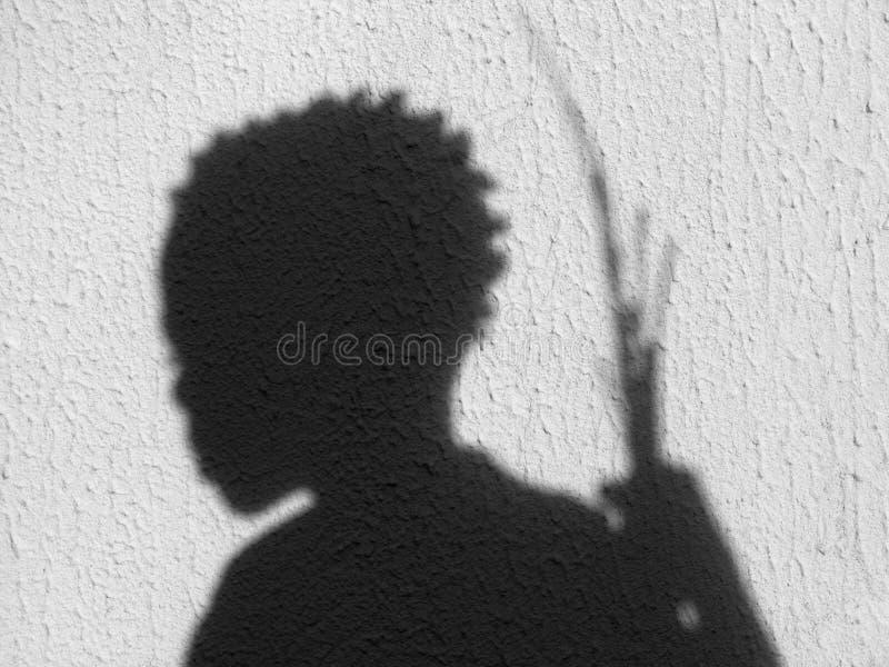 L'ombra di un ragazzo che tiene i bastoni sulla pietra fotografie stock libere da diritti
