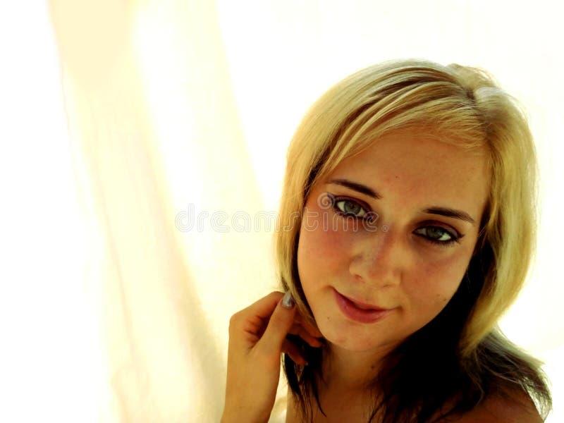L'ombre blond et noir d'une chevelure et le bleu ont observé la jeune femme avec le fond crème de texture image libre de droits