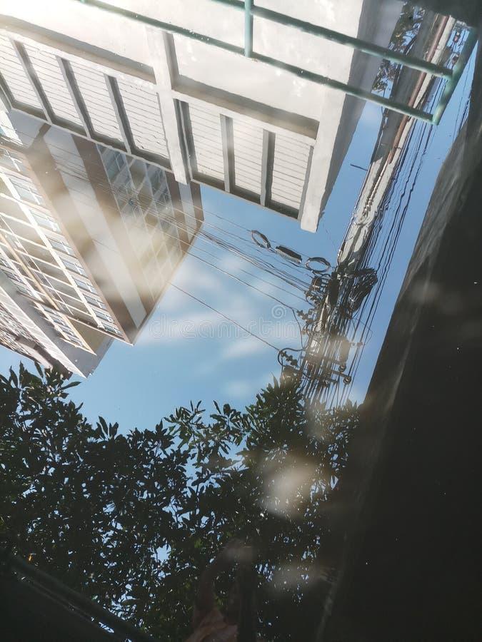 L'ombre de l'eau reflète le ciel pour voir le beau coin du bâtiment images libres de droits