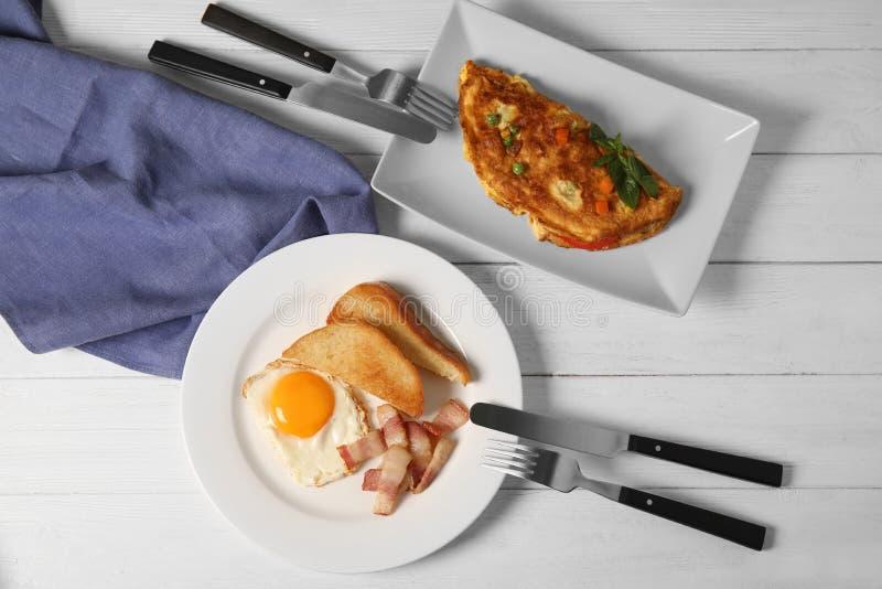 L'omelette, le uova fritte con bacon ed il pane tostato sono servito per la prima colazione fotografia stock libera da diritti