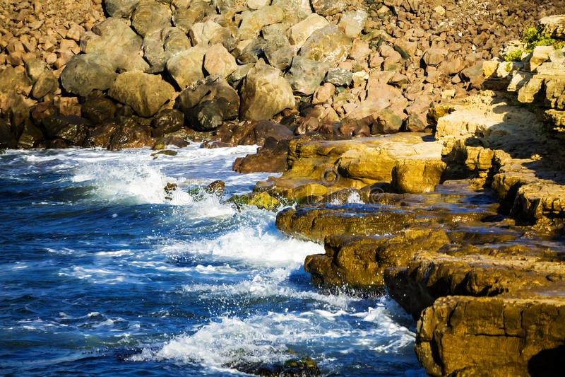 L'onda è ripartita nelle pietre fotografie stock