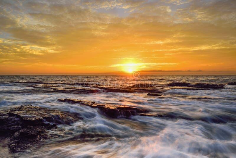 L'onda circola sulle rocce stagionate e sui massi a Narrabeen del nord fotografie stock