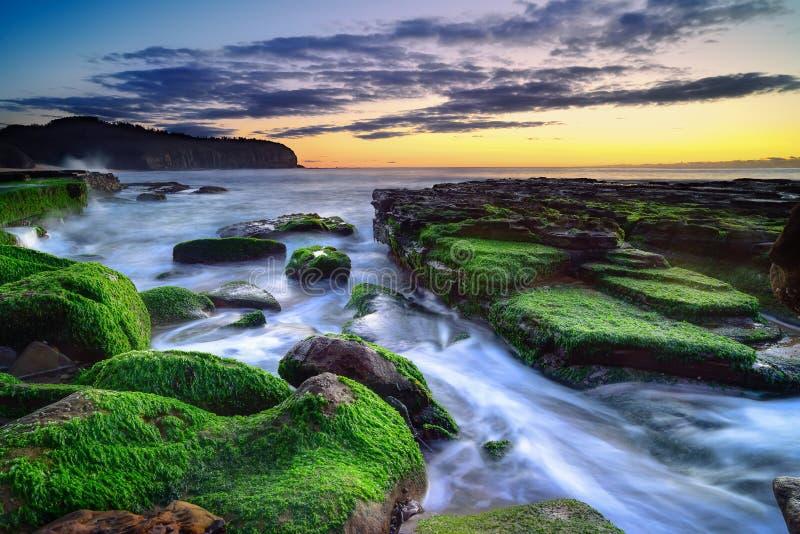 L'onda circola sulle rocce stagionate ed i massi a Turimetta sono fotografia stock