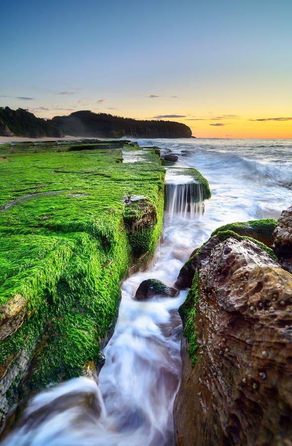 L'onda circola sulle rocce stagionate ed i massi a Turimetta sono immagine stock libera da diritti