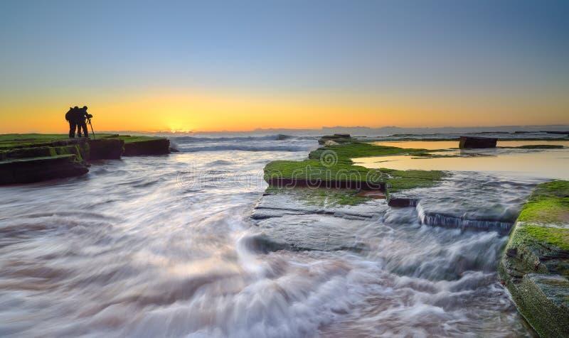 L'onda circola sulle rocce stagionate ed i massi a Turimetta sono fotografie stock libere da diritti