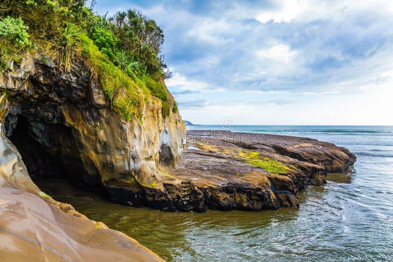 L'onda di marea ha sommerso la caverna sulla spiaggia fotografia stock