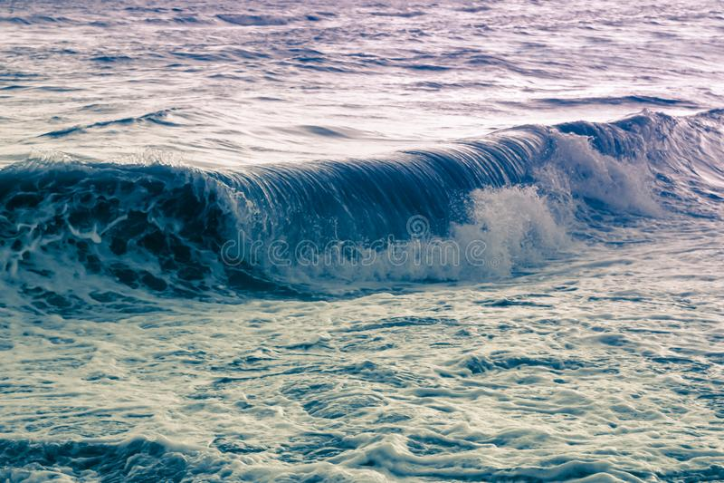 L'onda di turbine porpora blu del mare sommerge la riva, un seasca surreale fotografia stock libera da diritti