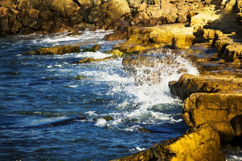 L'onda ? ripartita nelle pietre fotografia stock