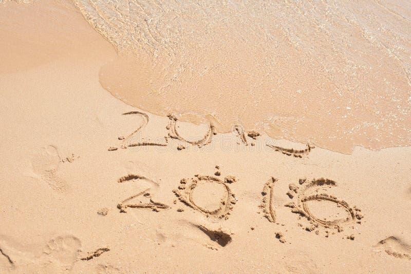 L'onda sta riguardando le cifre 2015 Concetto di nuovo anno Iscrizioni 2015 e 2016 su una sabbia della spiaggia Buon anno 2016 immagini stock