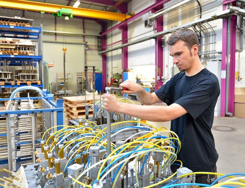 L'opérateur répare une machine dans un ensemble industriel avec des outils - p photo libre de droits