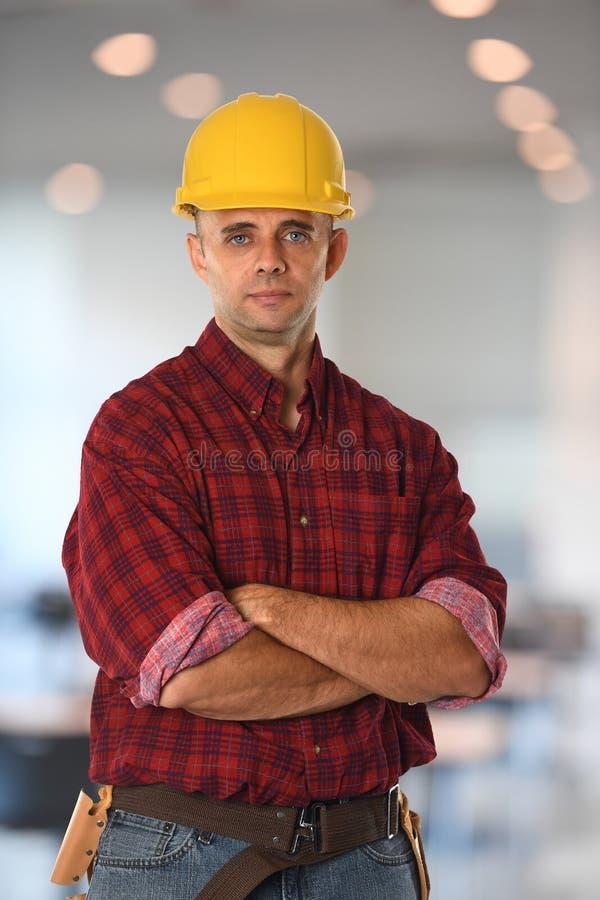 L'operaio di costruzione con le braccia ha attraversato immagine stock libera da diritti