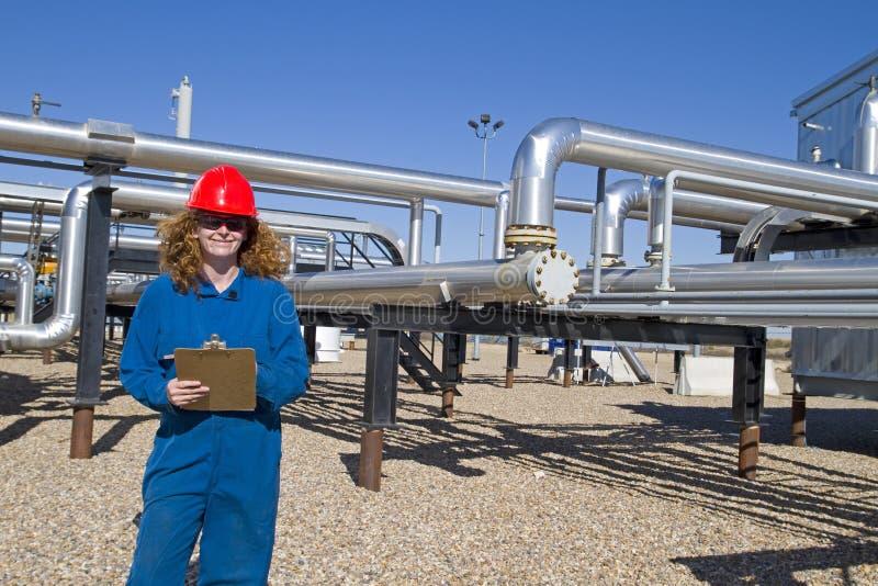 L'operatore femminile del giacimento di gas controlla il luogo del compressore fotografia stock