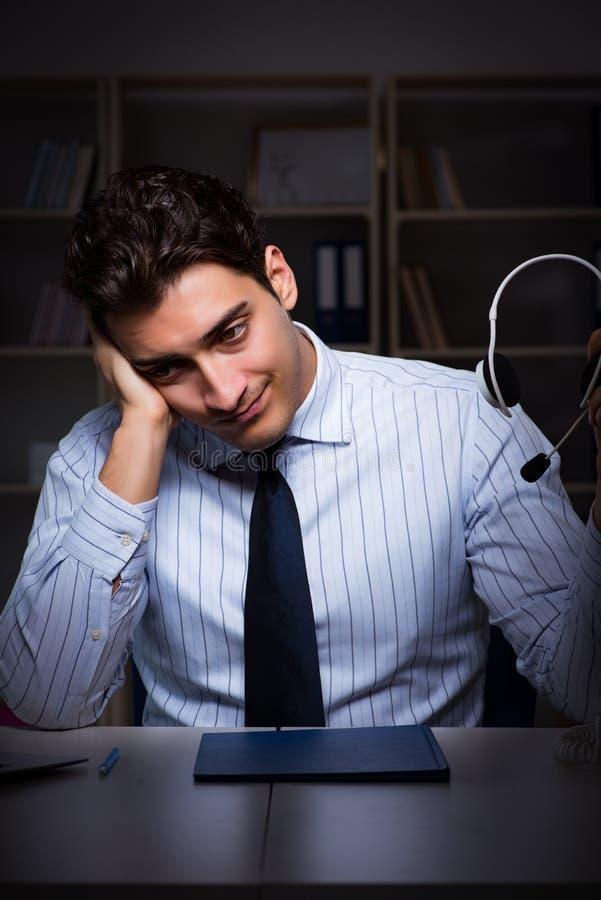 L'operatore stanco ed esaurito del servizio d'assistenza durante il turno di notte immagine stock libera da diritti