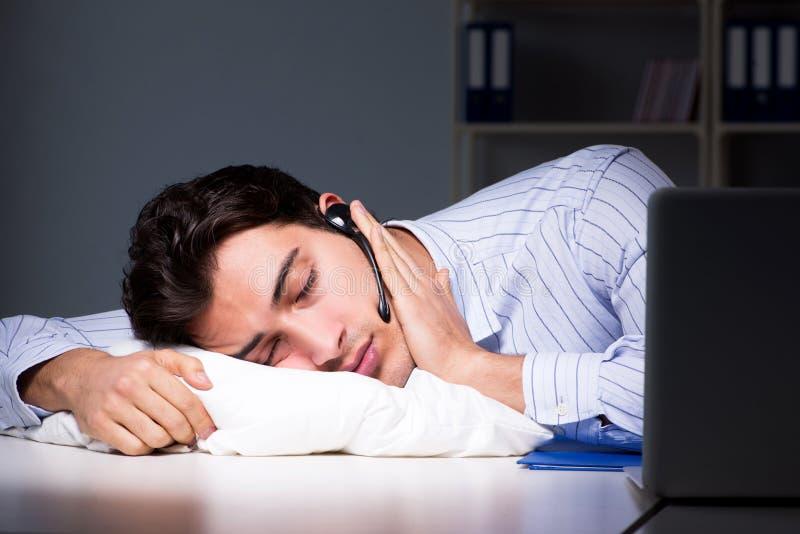 L'operatore stanco ed esaurito del servizio d'assistenza durante il turno di notte immagini stock libere da diritti