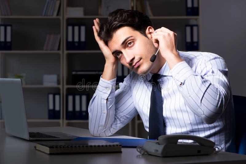 L'operatore stanco ed esaurito del servizio d'assistenza durante il turno di notte fotografia stock