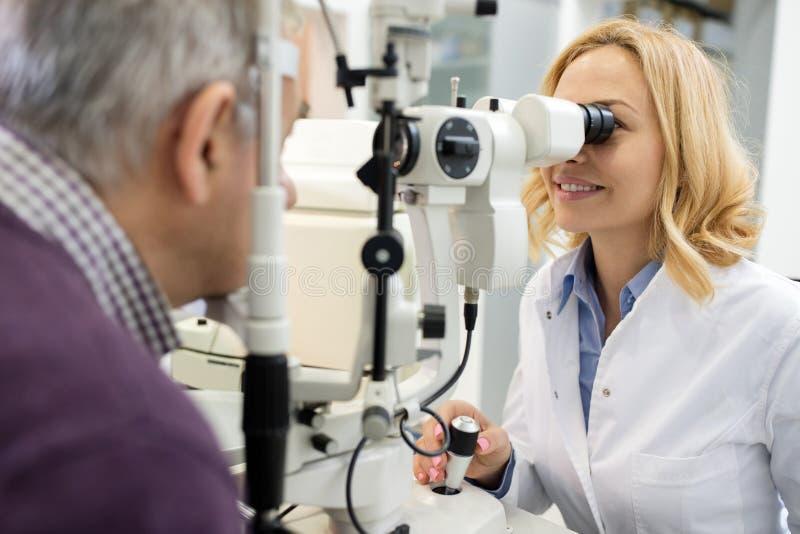 L'ophtalmologiste féminin regarde les yeux patients utilisant des appareils images stock