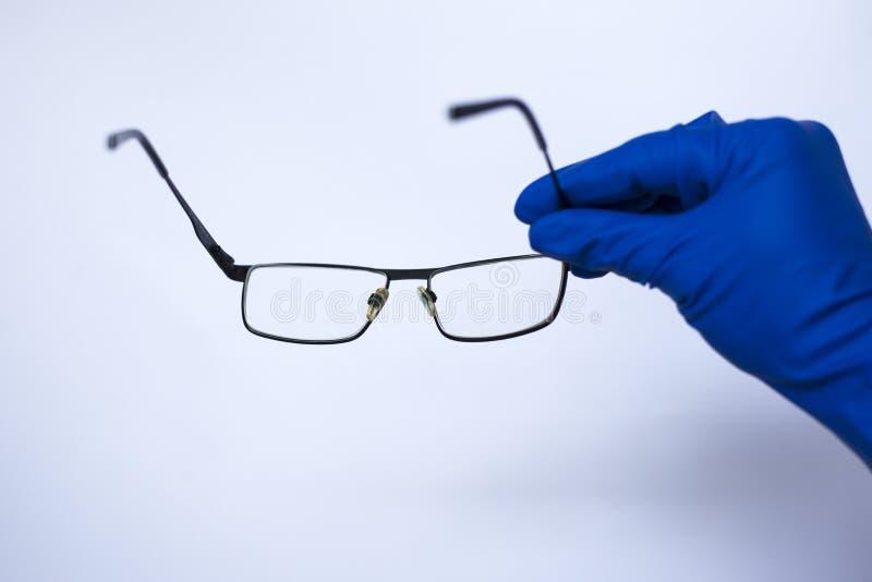 L'ophtalmologiste prend les lentilles au patient Verres astigmates pour la basse vision sur le fond blanc dans les gants m?dicaux photos stock