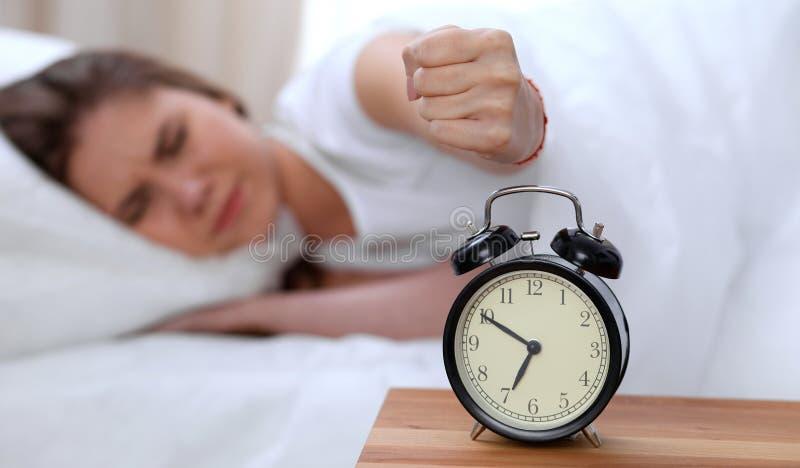 L'opposé de réveil de la jeune femme somnolente étirant la main au disposé de sonnerie d'alarme l'arrêtent Réveillez-vous tôt, pa photo libre de droits