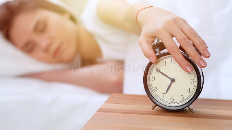L'opposé de réveil de la jeune femme somnolente étirant la main au disposé de sonnerie d'alarme l'arrêtent Réveillez-vous tôt, pa photos stock