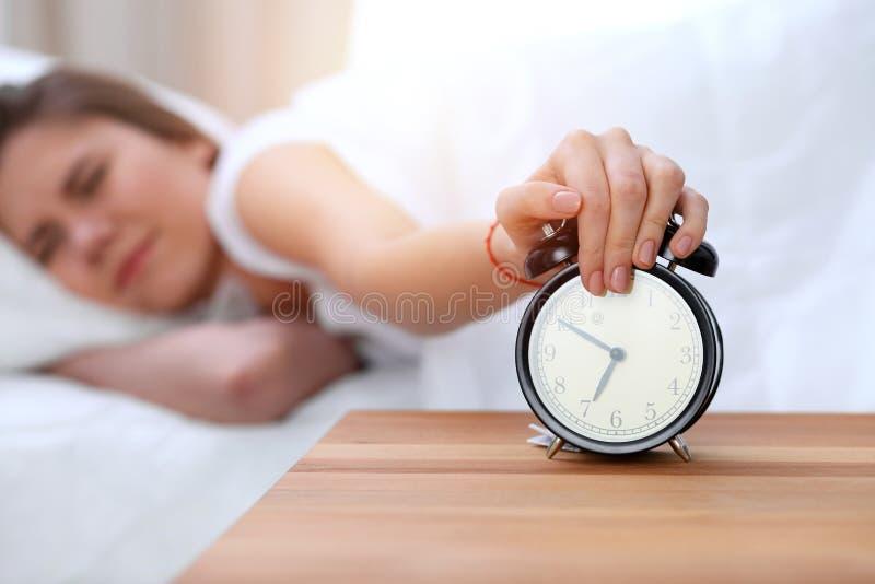 L'opposé de réveil de la jeune femme somnolente étirant la main au disposé de sonnerie d'alarme l'arrêtent Réveillez-vous tôt, pa photographie stock