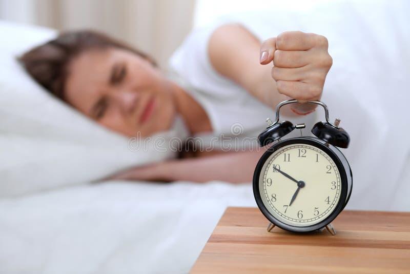 L'opposé de réveil de la jeune femme somnolente étirant la main au disposé de sonnerie d'alarme l'arrêtent Réveillez-vous tôt, pa photo stock