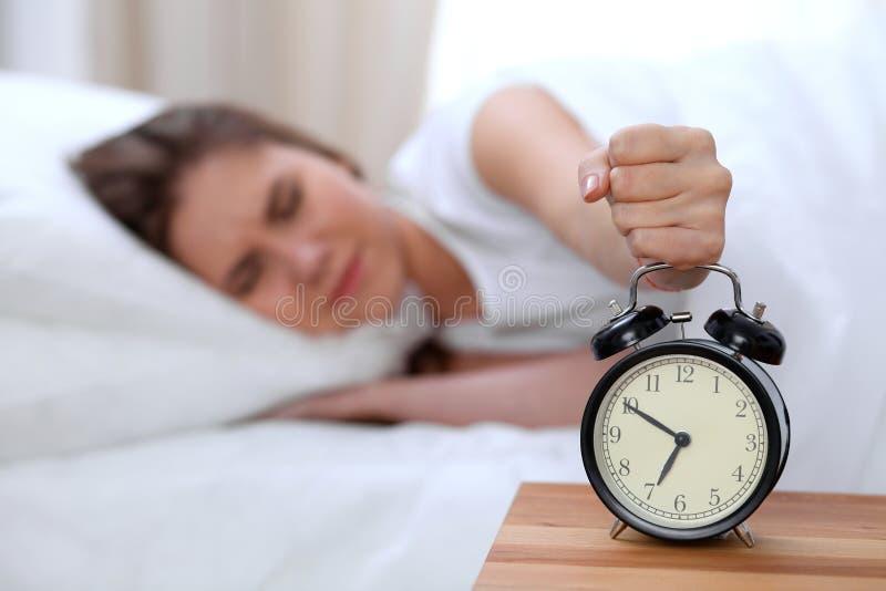 L'opposé de réveil de la jeune femme somnolente étirant la main au disposé de sonnerie d'alarme l'arrêtent Réveillez-vous tôt, pa photos libres de droits