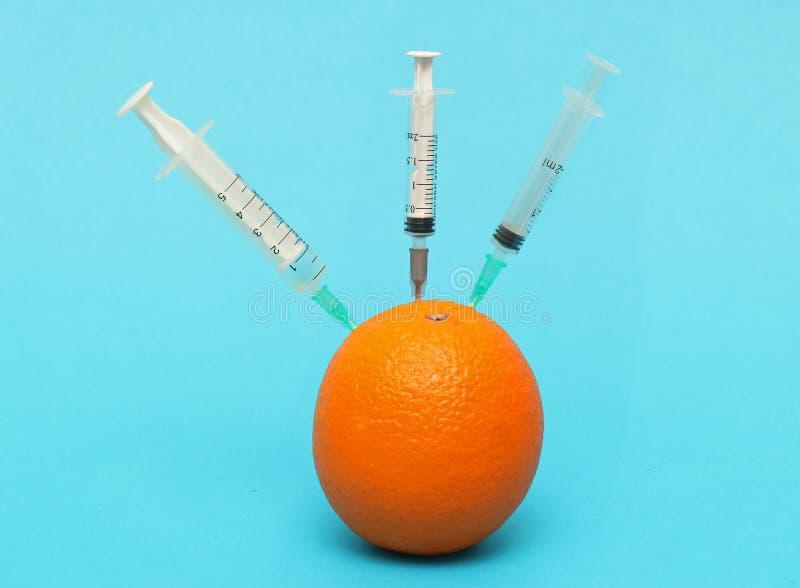 L'orange a injecté par des aiguilles images stock