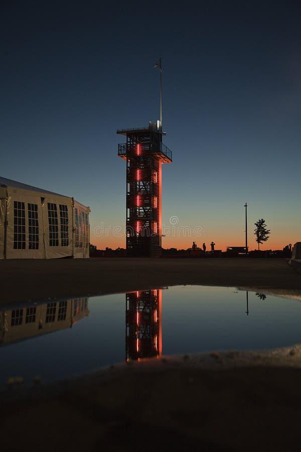 L'orange a mené la balise allumée se reflétant dans l'eau au coucher du soleil image libre de droits