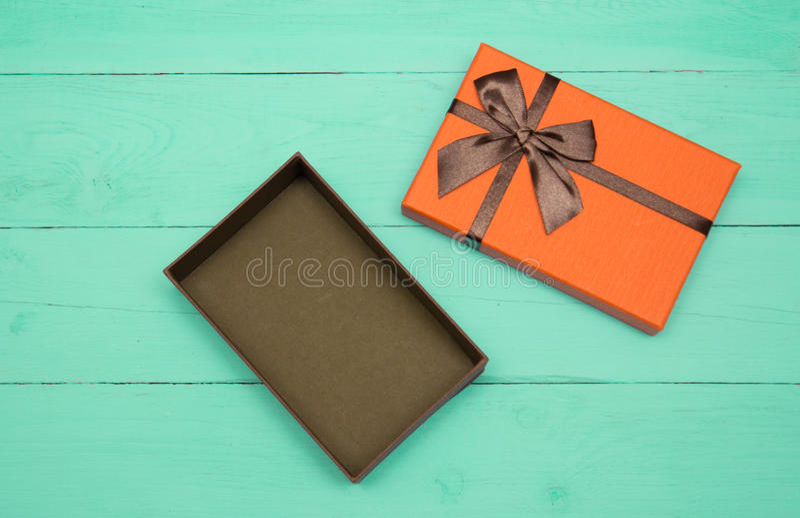 L'orange a ouvert le boîte-cadeau sur un fond en bois de turquoise images stock