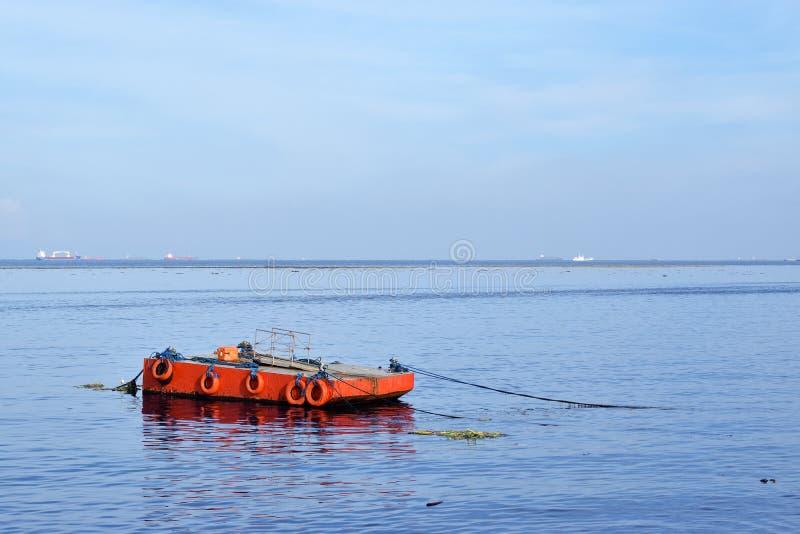 L'orange a peint la péniche en métal ancrée le long de la baie d'océan photo stock