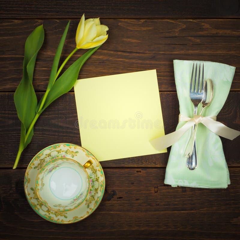 L'orario dell'alto tè dispone la regolazione con la tazza d'annata e piattino, tulipano giallo, argenteria, tovagliolo e carta i immagini stock libere da diritti
