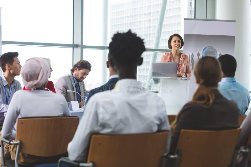 L'orateur femelle avec l'ordinateur portable parle dans un séminaire d'affaires photographie stock