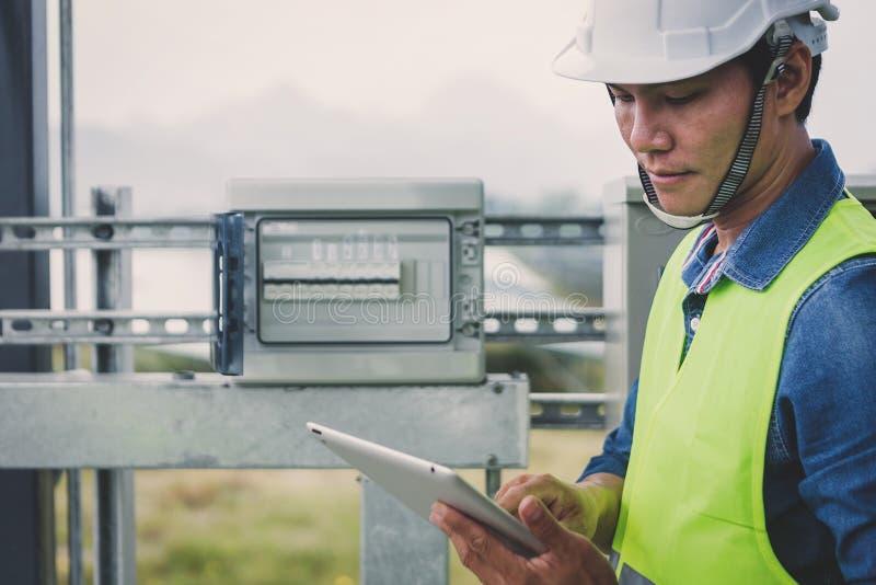 L'ordinateur portable de participation d'ingénieur ou d'électricien pour inspectent et vérifiant le conseil de distribution pr image libre de droits