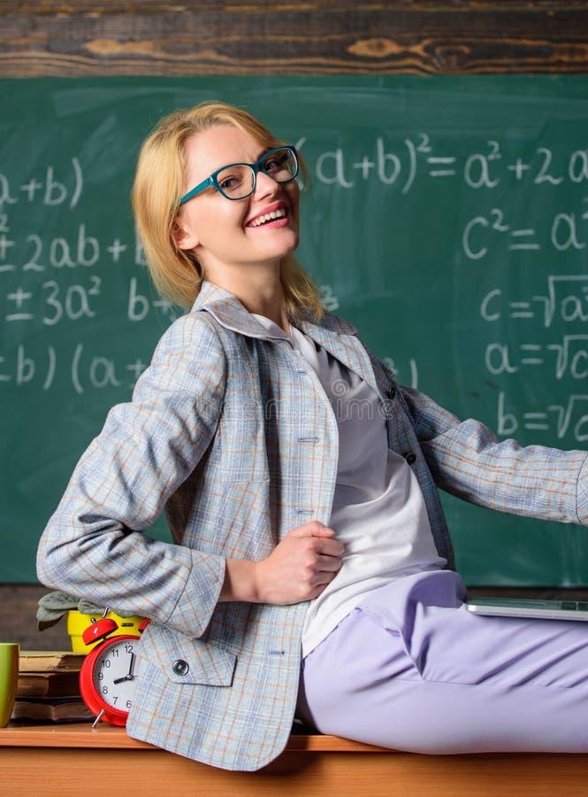L'ordinateur portable de prise de professeur de femme reposent le fond de tableau de salle de classe de table Professeur de génér photos libres de droits