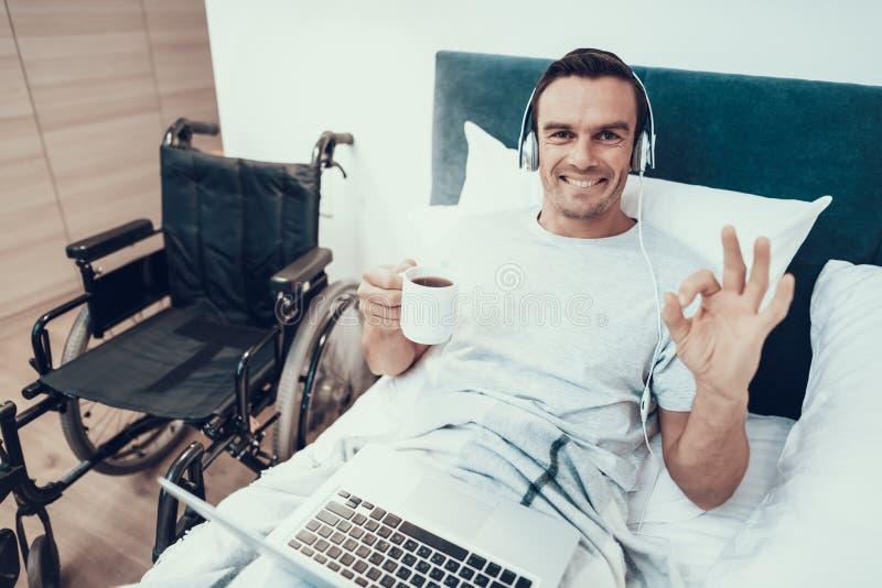 L'ordinateur portable handicapé d'utilisations d'homme dans le lit montre le geste CORRECT photos libres de droits