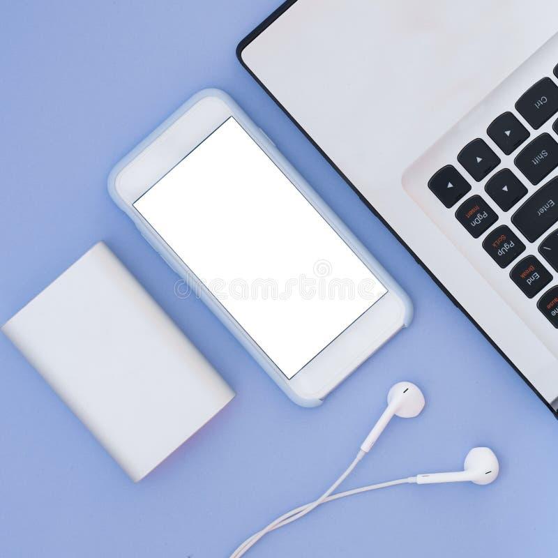 L'ordinateur portable, le téléphone, les écouteurs et la puissance encaissent sur un fond bleu Composition et endroit plats en co images stock