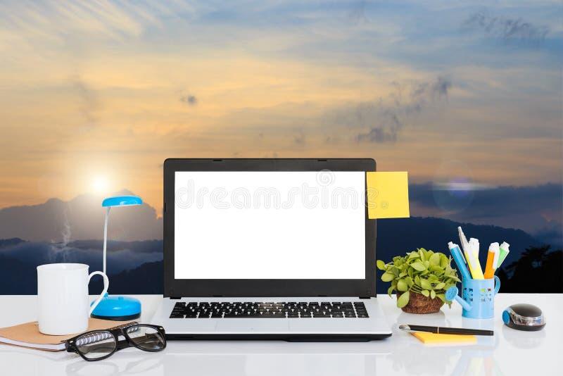 L'ordinateur portable sur le bureau et le paysage regardent le fond photographie stock