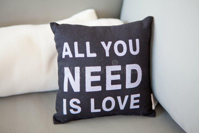 L'oreiller noir en gros plan avec une inscription tout que vous avez besoin est amour sur un divan léger avec des oreillers, foye photos libres de droits