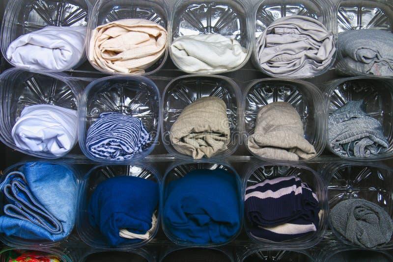 L'organisation du stockage des vêtements dans le cabinet sur l'étagère Utilisation secondaire des bouteilles en plastique L'espac photos stock