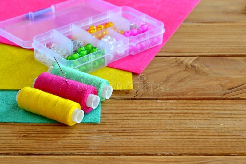 L'organizzatore con le varie perle, filo colorato, ago, feltro collega immagine stock