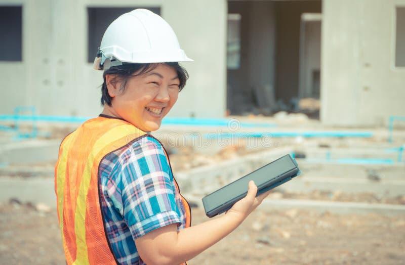 L'organizzazione asiatica delle donne tiene una compressa per uso nell'ispezione dei cantieri per accuratezza e conformemente al  fotografie stock