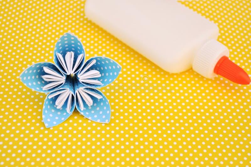L'origami bleu fleurit et colle la bouteille sur le fond jaune photographie stock libre de droits