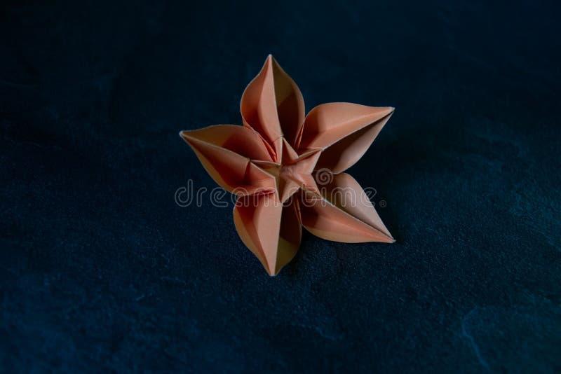 L'origami fleurit la fleur - art de papier sur le fond texturisé photos stock