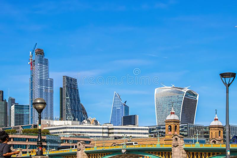 L'orizzonte delle costruzioni moderne a Londra ha osservato sopra il ponte di Londra sotto bello cielo blu fotografie stock