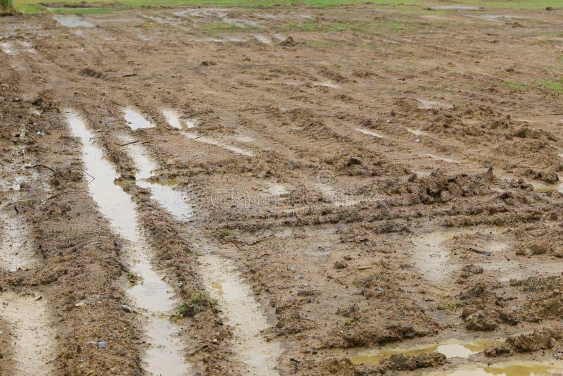 L'orma della ruota sopra riempie il suolo dopo la pioggia fotografie stock