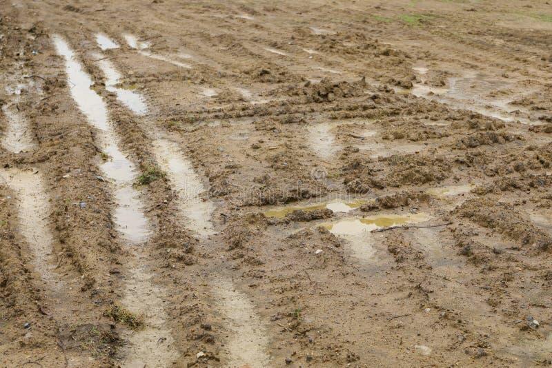 L'orma della ruota sopra riempie il suolo dopo la pioggia immagini stock libere da diritti